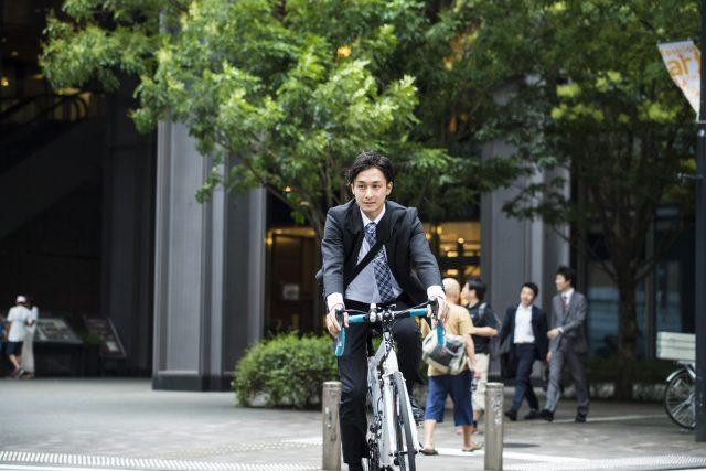 Cool businessman is riding the road bike